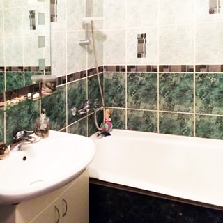 На фото: часть помещения ванной комнаты, прямо у стены - ванная со смесителем, настенной стойкой и гибким шлангом для лейки, слева от нее керамическая раковина на тумбе с дверцами, на раковине свой смеситель, над раковиной настенное зеркало с полкой, стены облицованы керамической плиткой