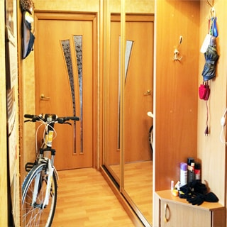 На фото: часть помещения прихожей, справа у стены - одежный шкаф-купе, правее - вешалка для одежды и тумбочка для обуви, слева у стены - велосипед, прямо - дверь в комнату, полы - ламинат
