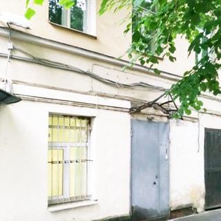 На фото: часть фасада (два этажа) здания, стена оштукатурена, в цокольном этаже - входная двустворчатая металлическая дверь серого цвета с замком, звонком, фонарем уличного освещения и остовом защитного козырька, слева от двери - окно с установленным стеклопакетом и защитной решеткой, на переднем плане - ветки лиственного дерева