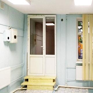 На фото: часть нежилого помещения, выход из помещения с установленным полуторастворчатым стеклопластиковым дверным блоком, пол в помещении на две ступеньки ниже уровня выхода, справа от двери - окно с установленным стеклопакетом, окно закрыто вертикальными жалюзи, под окном и слева от двери на стене - батареи центрального отопления, слева от двери на стене - электрощиток в защитном коробе, стены и потолок окрашены, полы - линолеум, на потолке - офисные блочные светильники дневного света