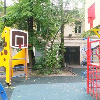 На фото: часть дворовой территории, занятая детской площадкой с покрытием, оборудованной элементами детско-спортивного городка, на заднем плане фасад двухэтажного дома и огороженный газон с кустами и деревьями, по фасаду дома - окна, двери, ворота
