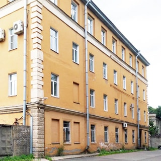 На фото: часть фасада четырехэтажного кирпичного здания, фасад оштукатурен, окна - стеклопакеты, на окнах первого этажа - защитные решетки, один вход под козырьком, слева к зданию примыкает кирпично-бетонный забор, территория перед зданием асфальтирована