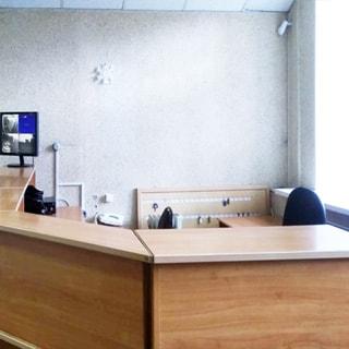 На фото: часть помещения офисного типа, стойка администратора, на стойке - монитор камер наружного наблюдения, за стойкой - офисное кресло и щит с ключами от помещений, справа - окно, стены - окрашены, потолки - подвесные
