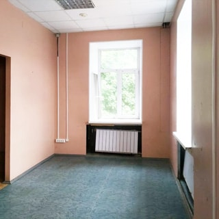 На фото: часть помещения офисного типа без мебели, два окна, под окнами - радиаторы батарей центрального отопления, полы - линолеум, стены окрашены, потолки - подвесные, на потолке - блочные светильники дневного света и датчик пожарной сигнализации