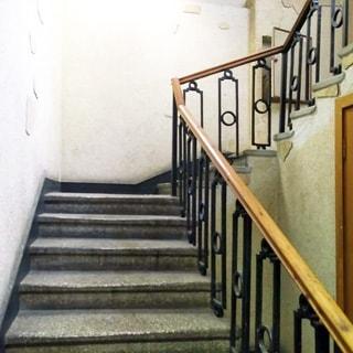 На фото: часть трехмаршевого лестничного пролета между этажами, лестница - бетонная, перила - деревянные по металлическому ограждению, стены окрашены