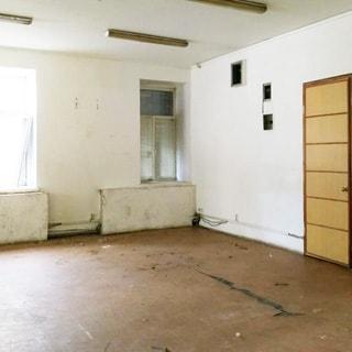 На фото: часть нежилого помещения, два окна, под окнами закрытые кожухами батареи центрального отопления, справа - входная дверь в помещение, полы - линолеум, стены и потолки окрашены, на потолке - блочные подвесные светильники дневного света