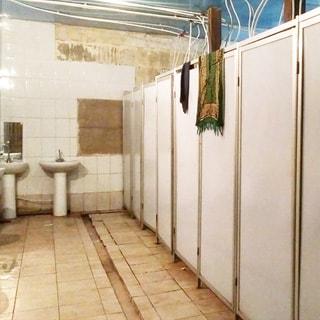 На фото: часть помещения санузла, полы и стены облицованы керамической плиткой, потолки - окрашены, прямо у стены - два умывальника на стойках, справа - душевые кабинки