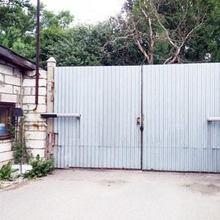 На фото: автоматизированные металлические распашные ворота со стороны территории двора, слева - помещение охраны и контроля пропуска на территорию, двор перед воротами асфальтирован, за воротами на дальнем плане - деревья