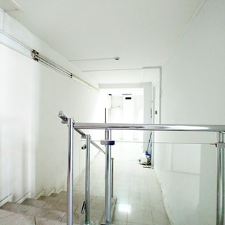 На фото: часть нежилого помещения - коридора, лестница шесть ступеней вниз с ограждением и перилами из металла и стекла, коридор прямоугольной вытянутой формы, стены и потолок окрашены, пол облицован плиткой, слева на стене у потолка - светильники дневного света, на потолке - датчик пожарной сигнализации, в глубине коридора слева и справа - открытые двери в соседние помещения