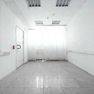 На фото: часть нежилого помещения офисного типа, одно окно закрыто вертикальными жалюзи до пола, слева - металлическая дверь в соседнее помещение, стены окрашены, по стенам на высоте около метра параллельно полу проложены кабель-каналы с выводом розеток на рабочие места, потолки - подвесные с вмонтированными светильниками дневного света офисного типа, на потолке установлены датчики пожарной сигнализации, полы облицованы плиткой