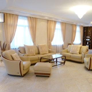 На фото: часть помещения жилой комнаты - гостиной, три окна, мягкая мебель: два дивана и два кресла, журнальный столик со стеклянной столешницей, на потолке - люстра, полы - плитка