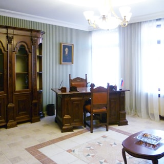 На фото: часть помещения жилой комнаты - кабинета, два окна, в углу у окна - двухтумбовый письменный стол, на столе - письменный прибор, у стола - два стула, слева у стены - книжный шкаф, на стене за столом картина в раме, полы - плитка, на переднем плане справа - журнальный столик, на потолке - люстра