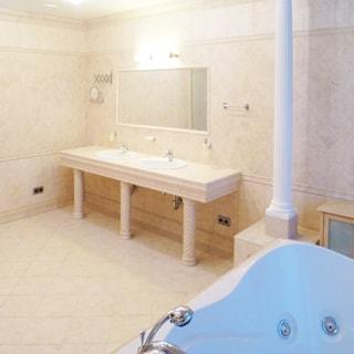На фото: часть помещения санузла, стены и пол - плитка, впереди у стены - массивная столешница с двумя раковинами со смесителями, над ними на стене - общее большое зеркало и светильники, на переднем плане - ванная - джакузи со смесителем