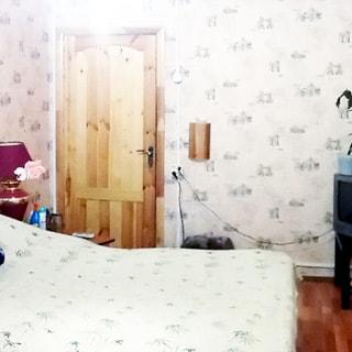 На фото: часть помещения жилой комнаты, на переднем плане - диван-кровать, прикроватная тумбочка с снастольной лампой, на заднем плане - дверь в комнату, справа у стены в углу тумбочка с телевизором на ней, стены оклеены обоями, полы - ламинат