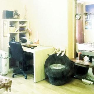 На фото: часть помещения жилой комнаты, письменный стол с офисным креслом, стеллаж с книгами, справа от стола - большое напольное зеркало, слева виден угол дивана, стены оклеены обоями, полы - ламинат